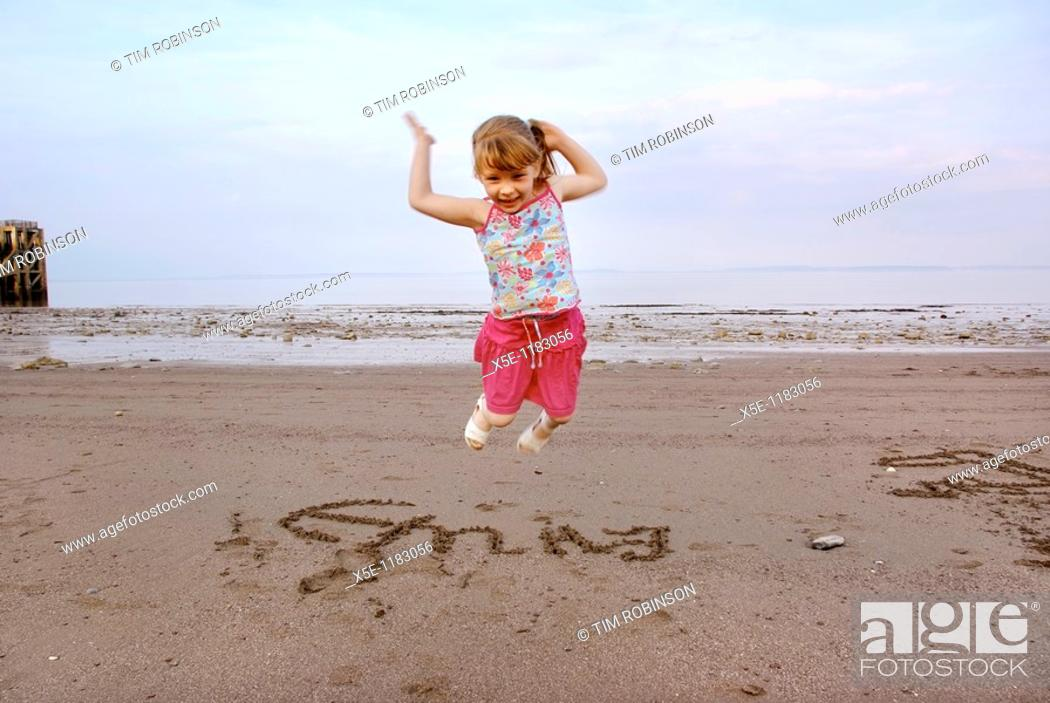 Stock Photo: 6 year girl jumping for joy on beach after writing her name in sand.