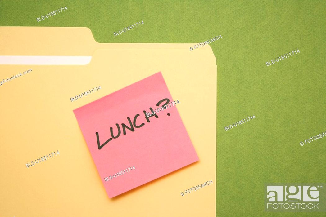 Stock Photo: Folder with pink sticky note reading lunch on a green background.