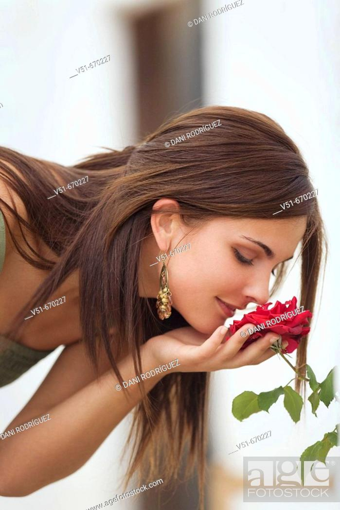 Stock Photo: Young woman smelling a flower.