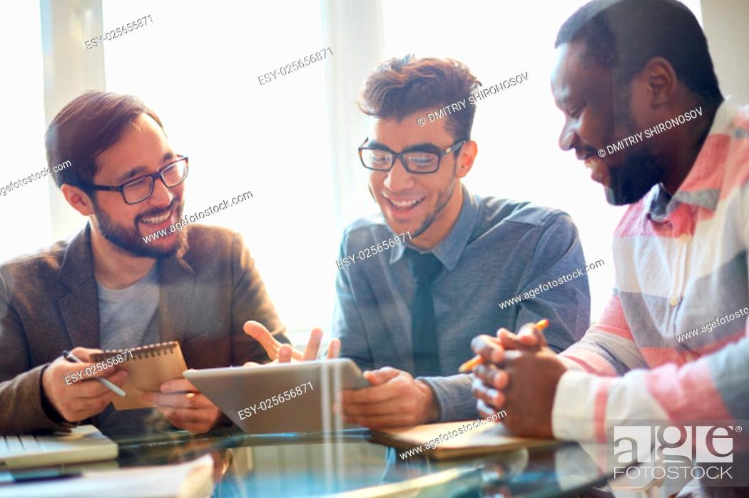 Stock Photo: Three businessmen discussing new project at meeting.