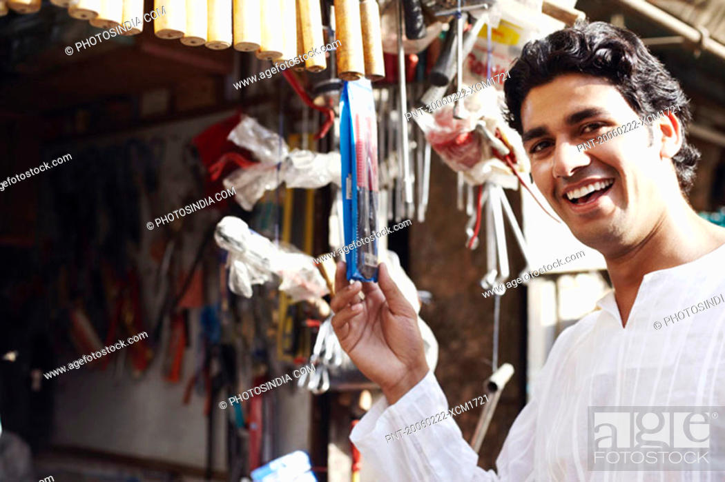 Stock Photo: Portrait of a young man holding a packet of work tools.