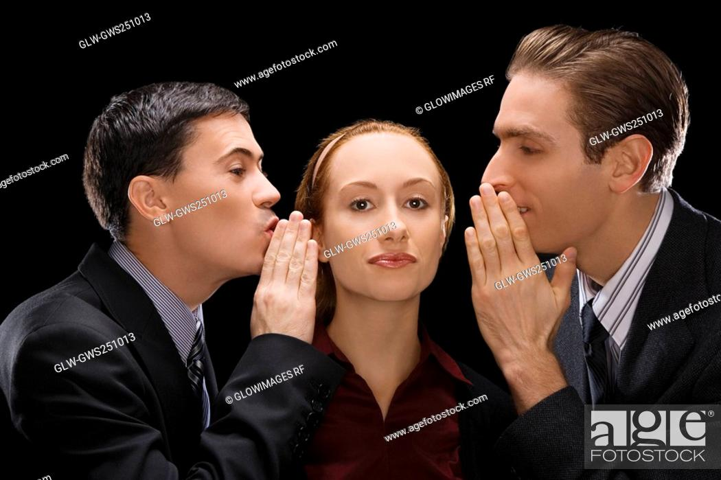 Stock Photo: Side profile of two businessmen whispering to a businesswoman.