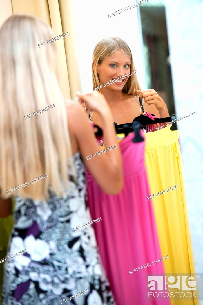 Stock Photo: Young woman trying dress on.