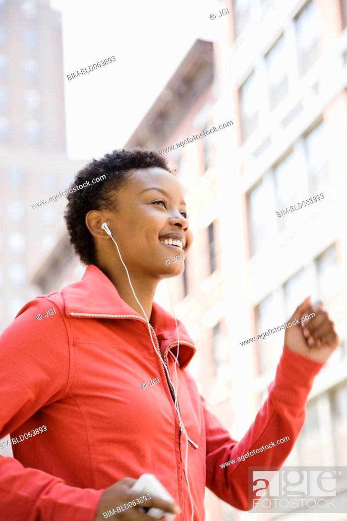 Stock Photo: African woman listening to mp3 player while walking outdoors.