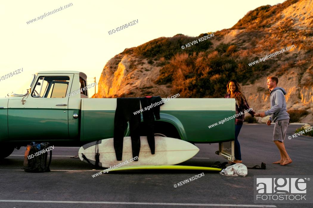 Stock Photo: Surfing couple with pickup truck at Newport Beach, California, USA.