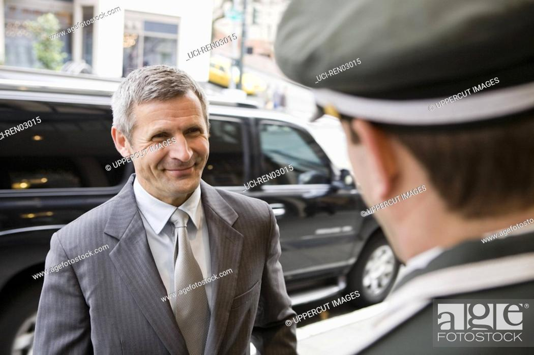 Stock Photo: Businessman smiling at bellhop.
