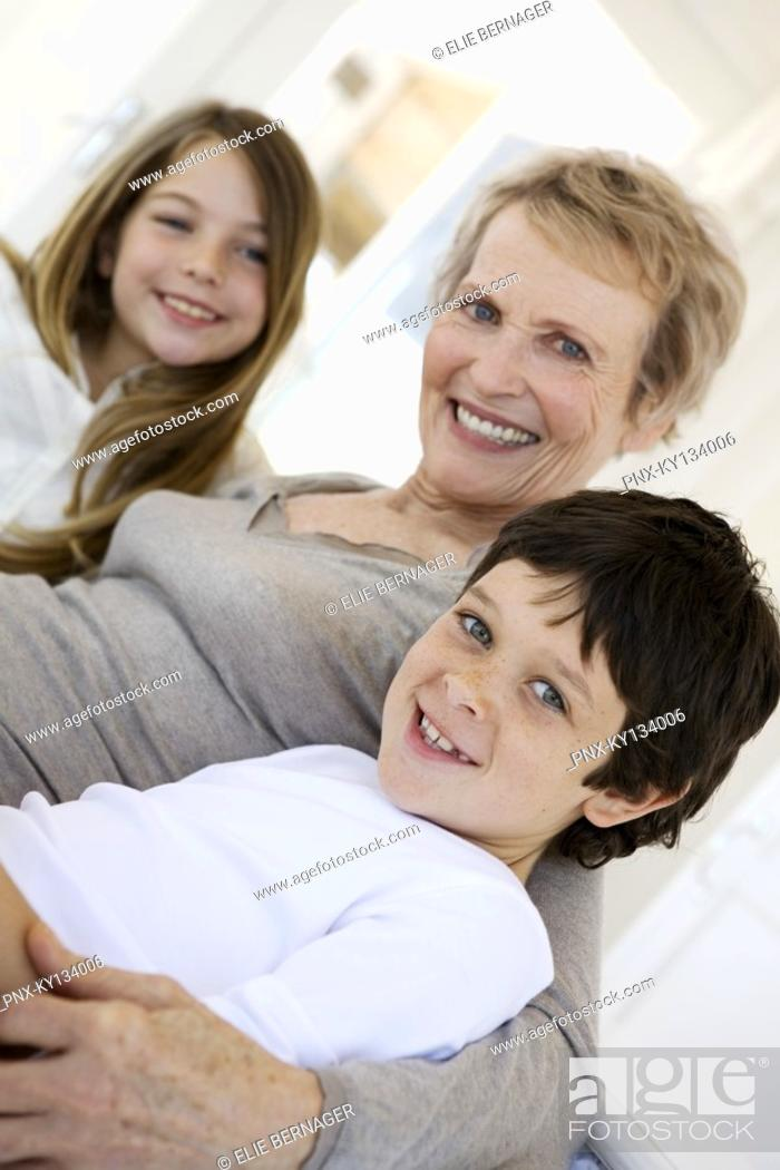 Stock Photo: Senior woman and two children smiling for the camera, indoors.
