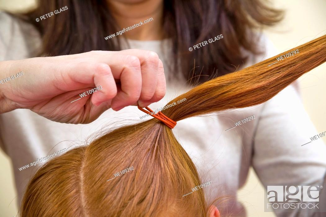 Stock Photo: Mother adjusting the hair of her preteen redhead daughter.