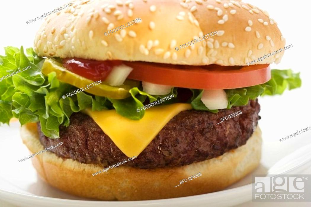 Stock Photo: Cheeseburger with tomato, onions and gherkin.