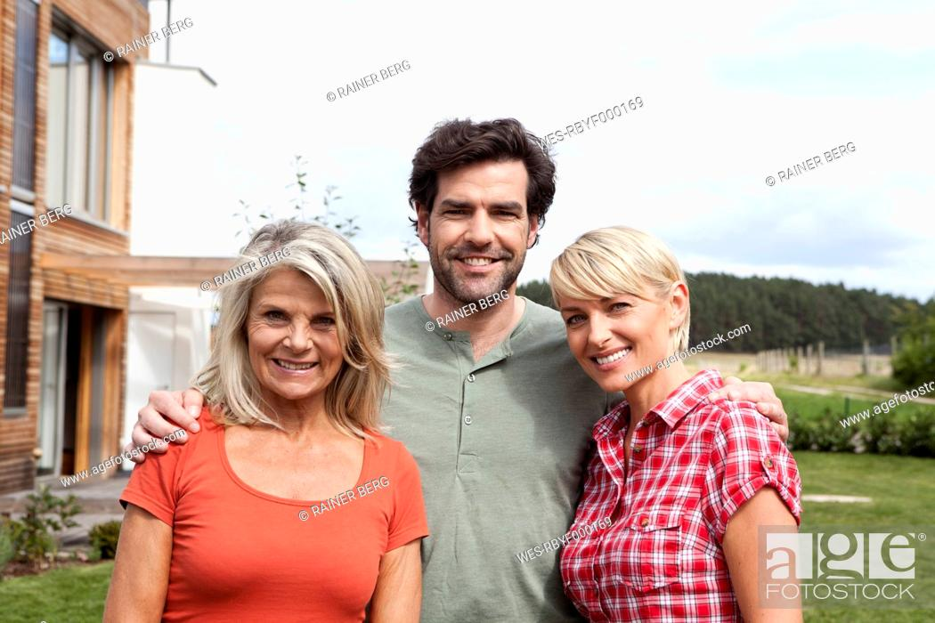 Stock Photo: Germany, Bavaria, Nuremberg, Family in front of house, smiling.