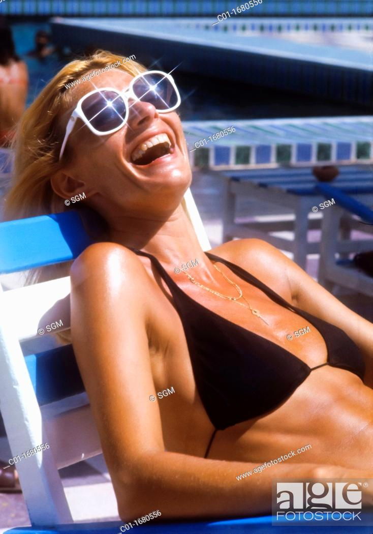 Stock Photo: Laughing woman with sunglasses and black swimsuit.