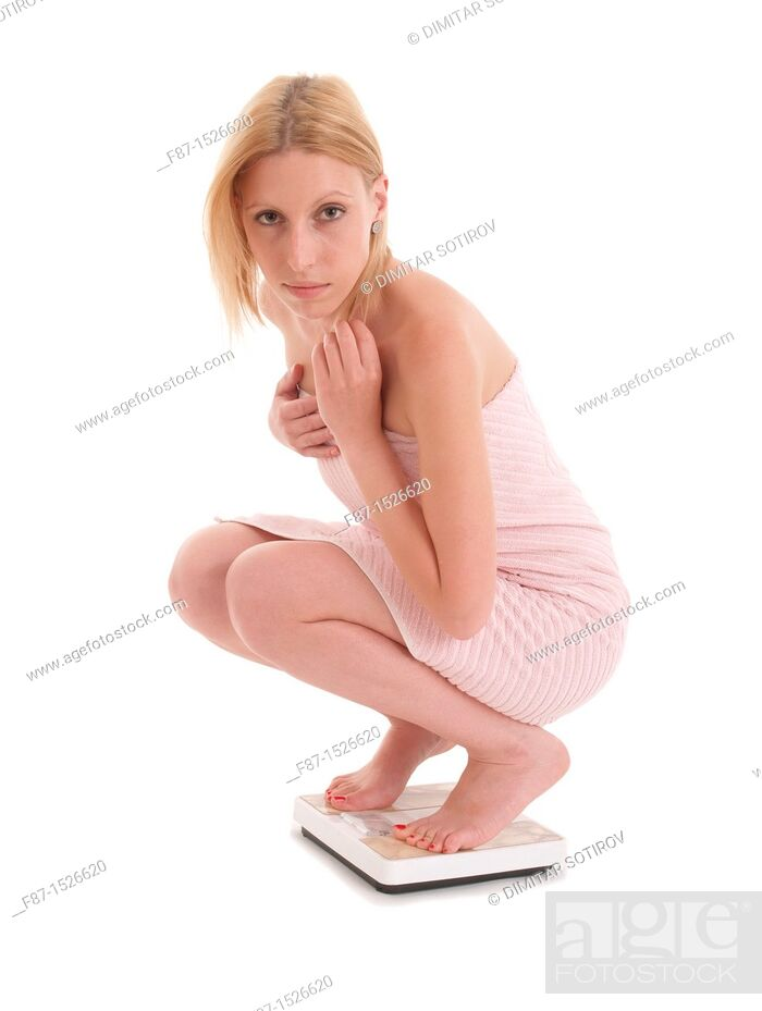 Stock Photo: Pretty young woman on scale, isolated on white background.
