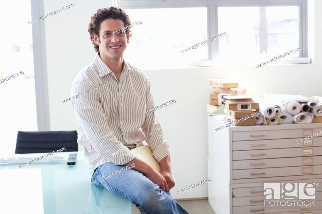 Stock Photo: Businessman sitting on desk in office.