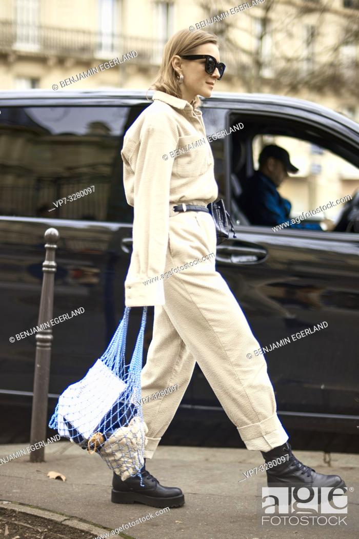 Stock Photo: fashionable blogger woman spotted on street at paris fashion week, wearing latest fashion trend, beige overall jumpsuit and net handbag, in Paris, France.