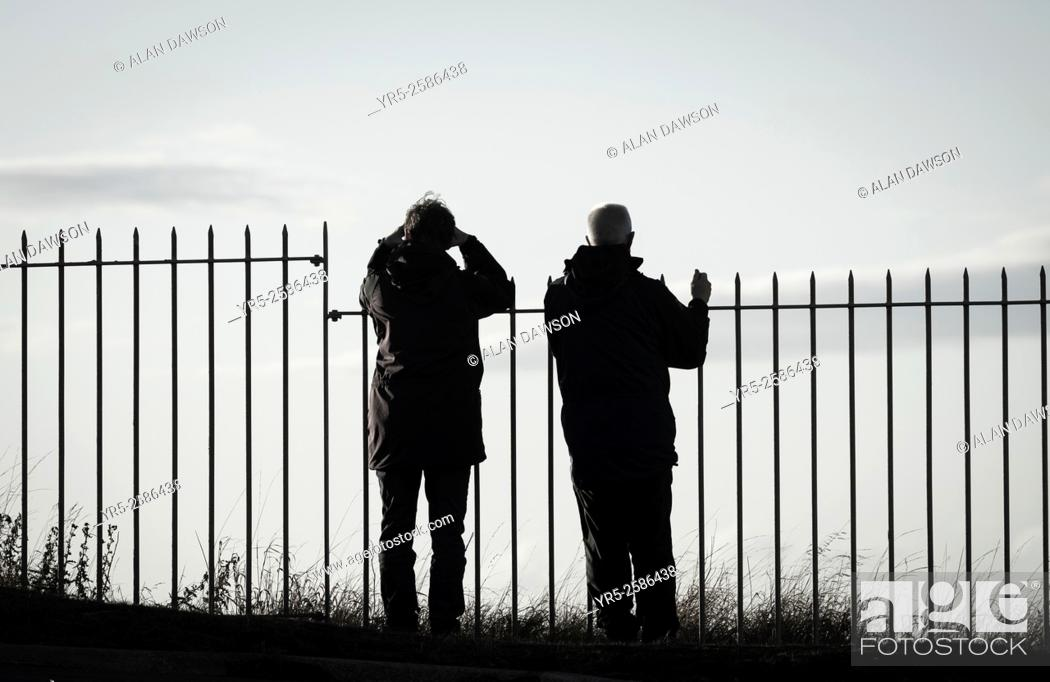 Stock Photo: Couple looking out to sea from Boulby Cliffs, among the highest sea cliffs in England, near Staithes, North Yorkshire, England, United Kingdom.