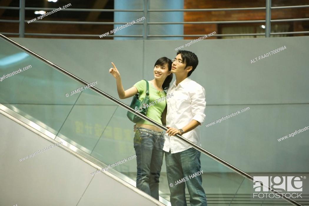 Stock Photo: Couple taking escalator in shopping mall, woman pointing out of frame.
