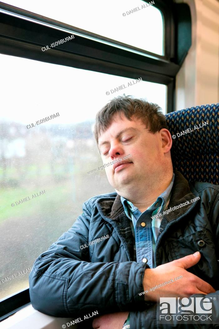 Stock Photo: Man with down syndrome sleeping on train.