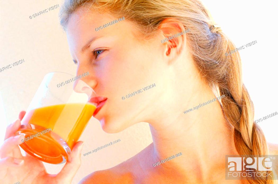 Stock Photo: Young woman drinking orange juice.