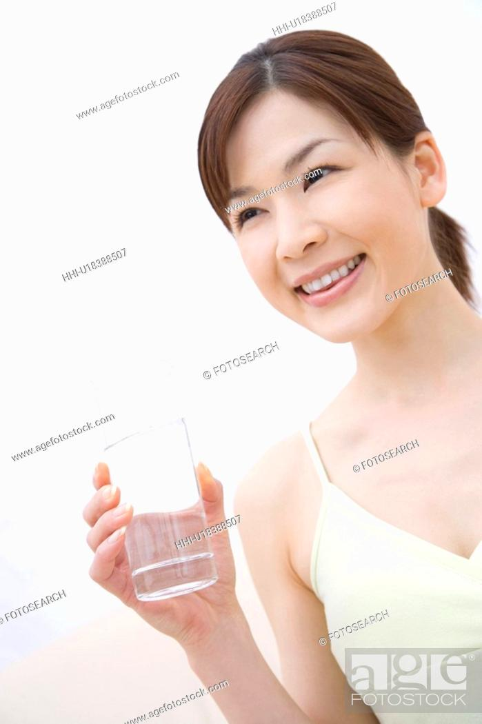 Stock Photo: Young woman holding a cup of water, front view.