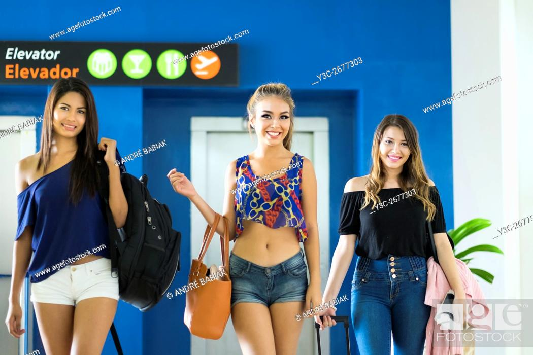 Stock Photo: Three female teenagers with luggange are coming out of an elevator at airport terminal.