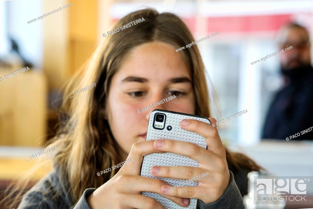 Imagen: girl looking at mobile phone, Castellon.