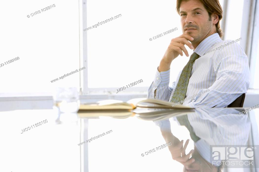 Stock Photo: Business man sitting at conference table portrait.
