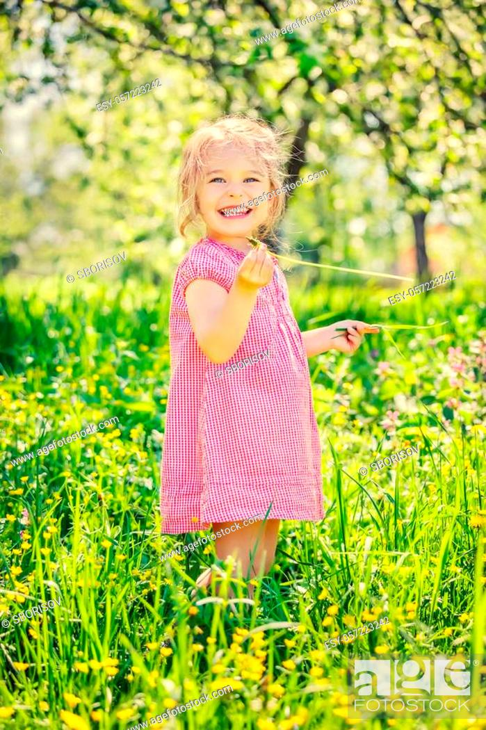 Stock Photo: Happy little girl playing in sunny spring garden.