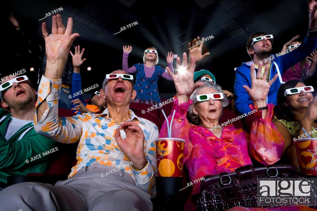 Stock Photo: Movie audience in 3D glasses, making faces, arms raised, low angle view.
