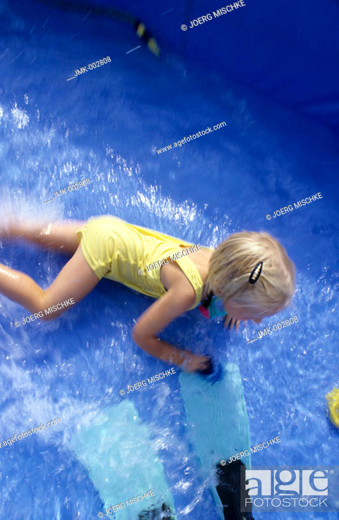 Stock Photo: A child, little girl, 5-10 years old, playing in a swimming pool in the garden.