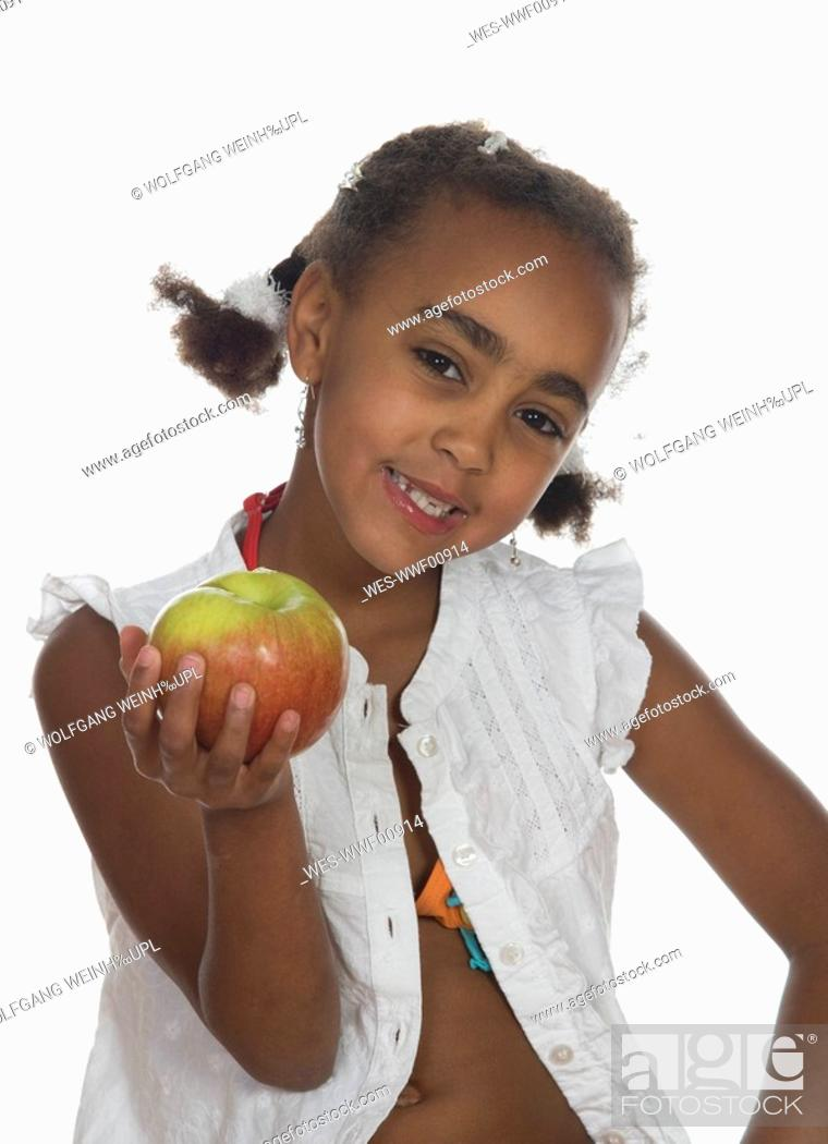 Stock Photo: African girl 6-7 holding apple, smiling, portrait.