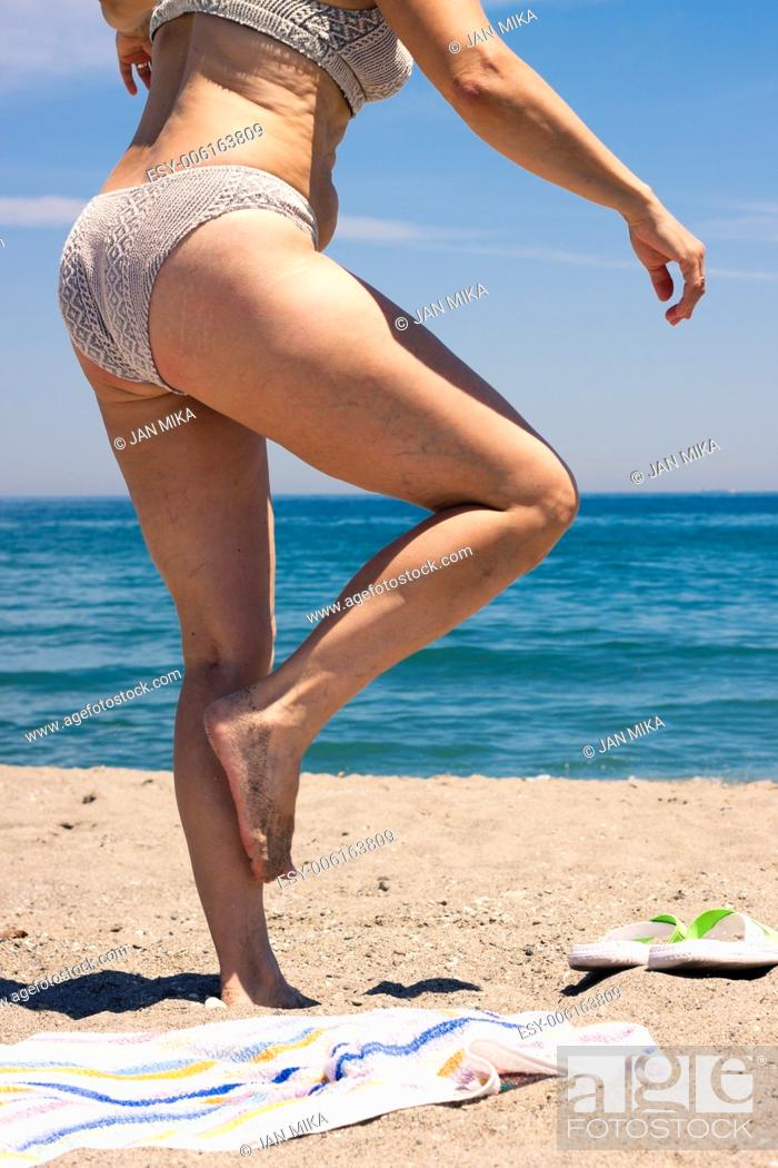Stock Photo: Detail of middle aged woman walking on the sandy beach.