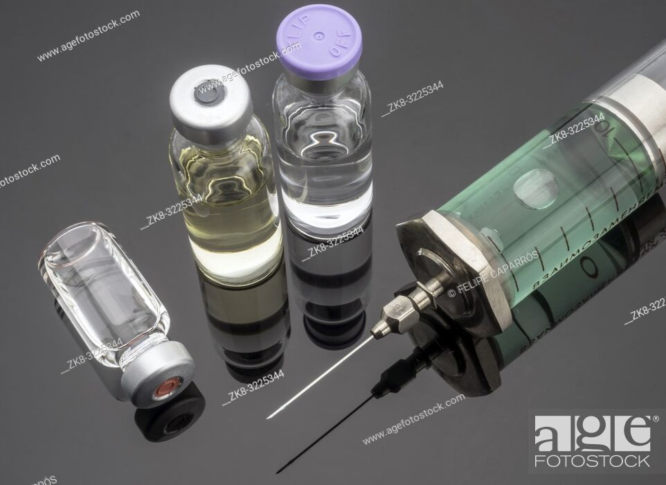 Stock Photo: Syringe vintage next to vials, conceptual image.
