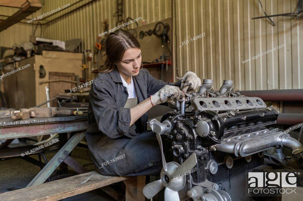 Stock Photo: Female mechanic repairing car engine at garage.