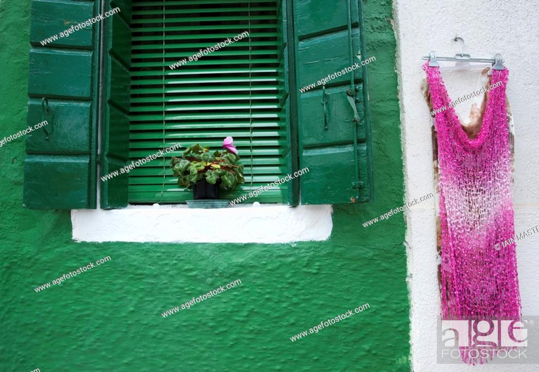 Stock Photo: Detail of dress hanging on wall beside painted window in Burano village near Venice Italy.