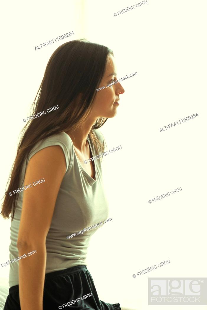 Stock Photo: Woman sitting on bed.