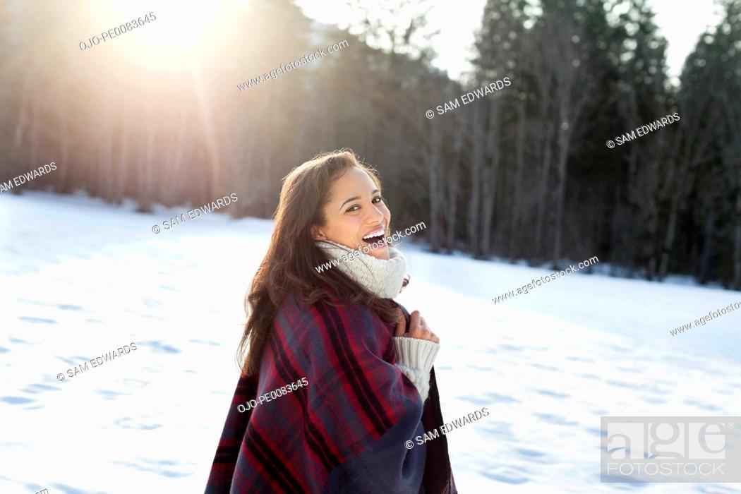 Stock Photo: Portrait of smiling woman walking in snowy field.