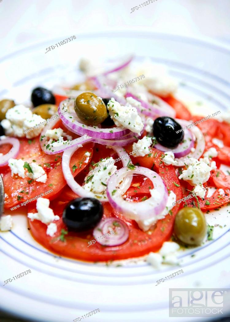 Stock Photo: Tomato salad with feta, olives and onions.
