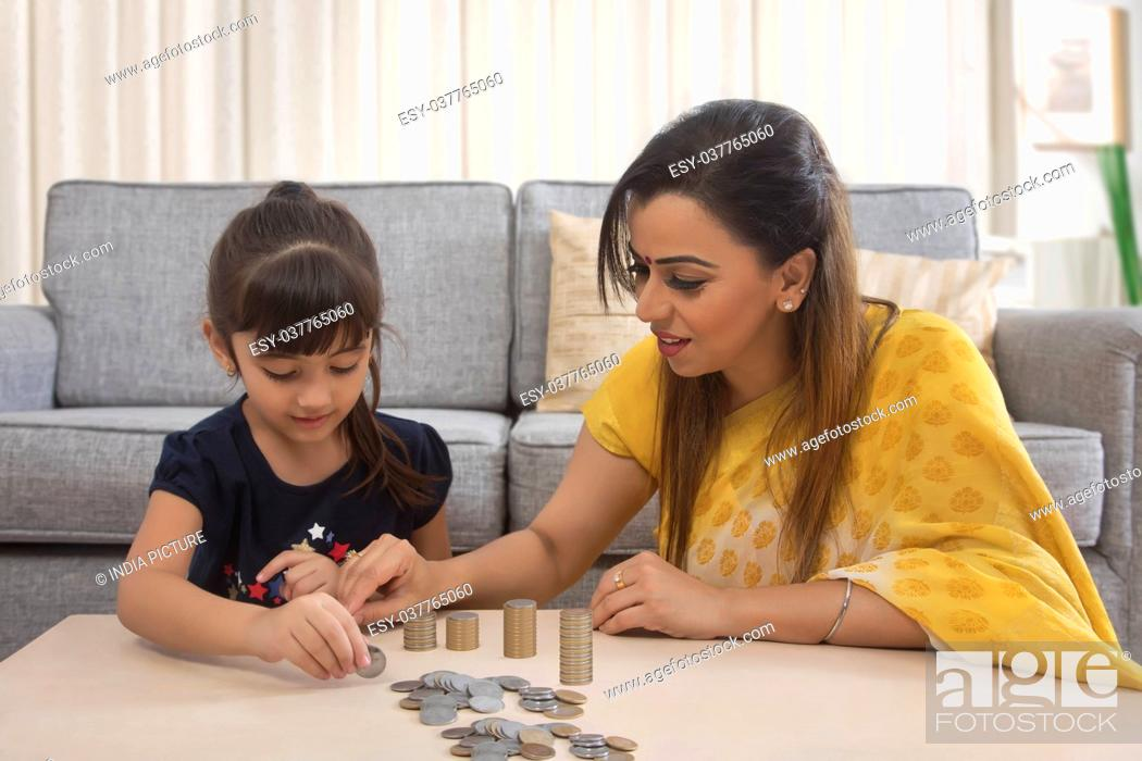 Stock Photo: Mother and daughter stacking coins at home.