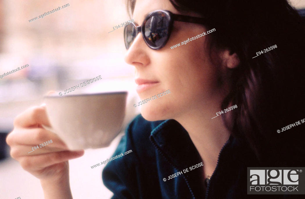 Photo de stock: profile of a Woman in a coffe shop holding a cup wearing sun glasses looking out of the window.