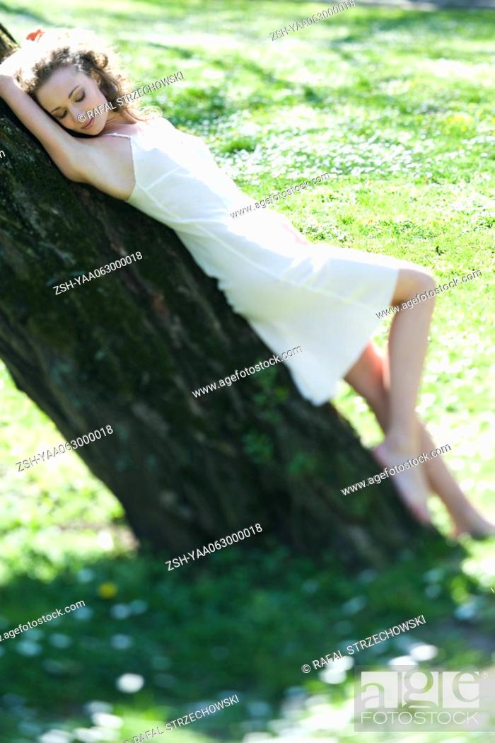 Stock Photo: Young woman in slip leaning against tree trunk, eyes closed.