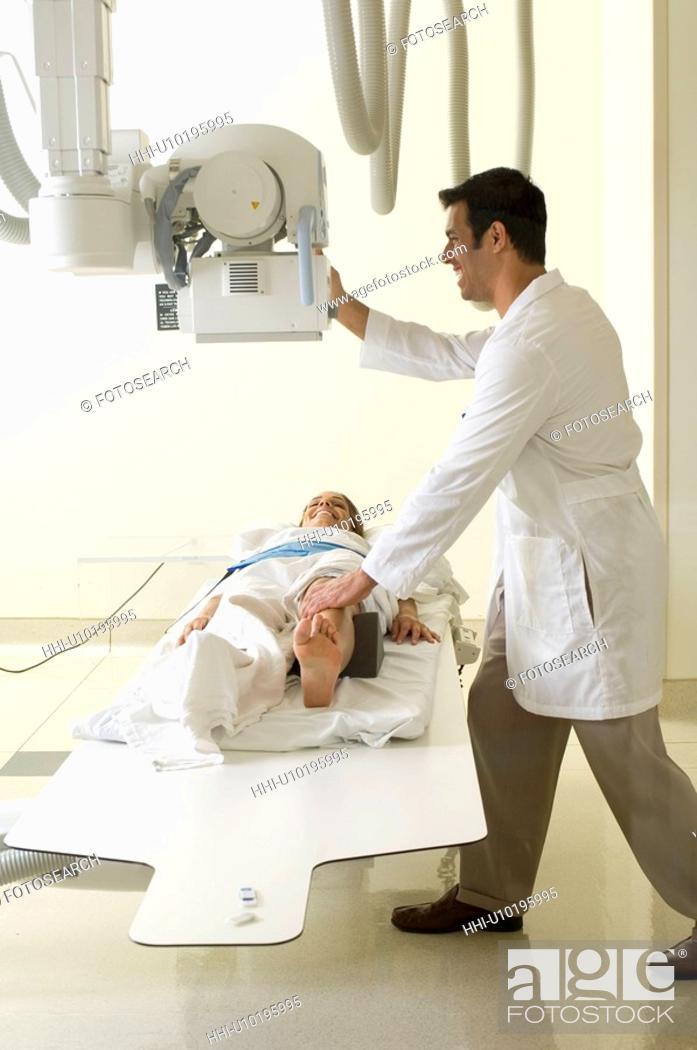 Stock Photo: Portrait of doctor examining patient's leg.