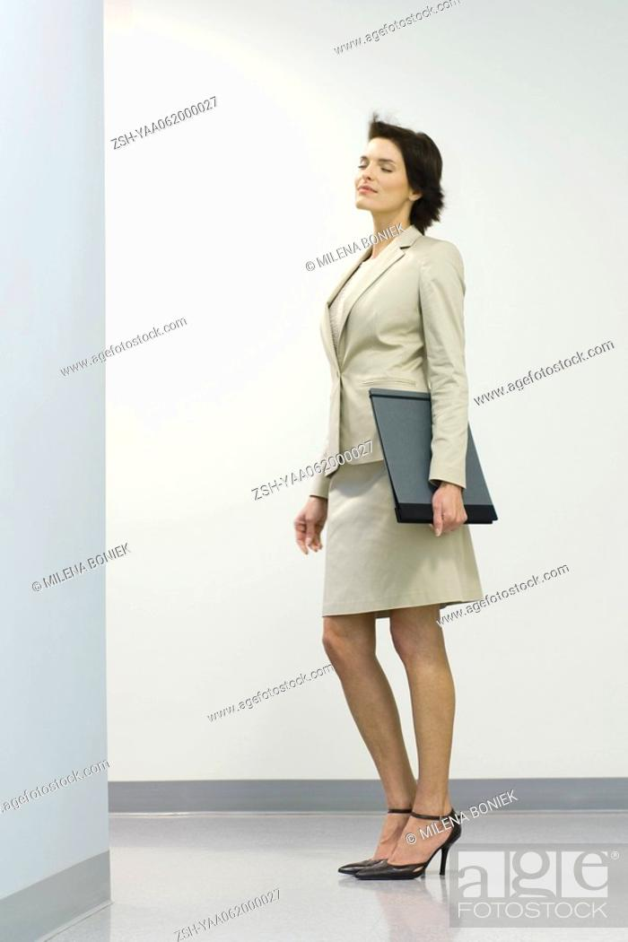 Stock Photo: Businesswoman standing in hallway with eyes closed, hair tousled by breeze.