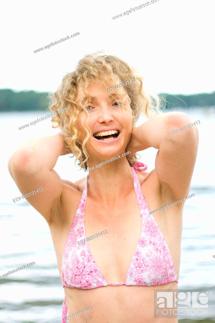 Stock Photo: Photo Of A Blond Curly Woman Having A Good Time Near Water.