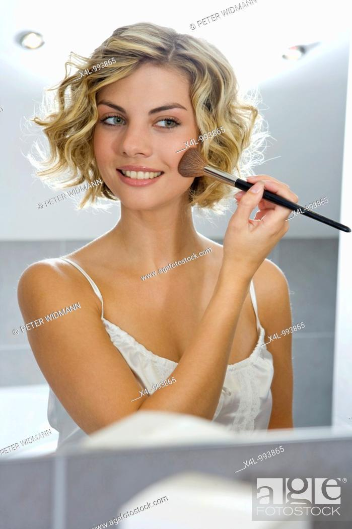 Stock Photo: woman putting on make up in bathroom.