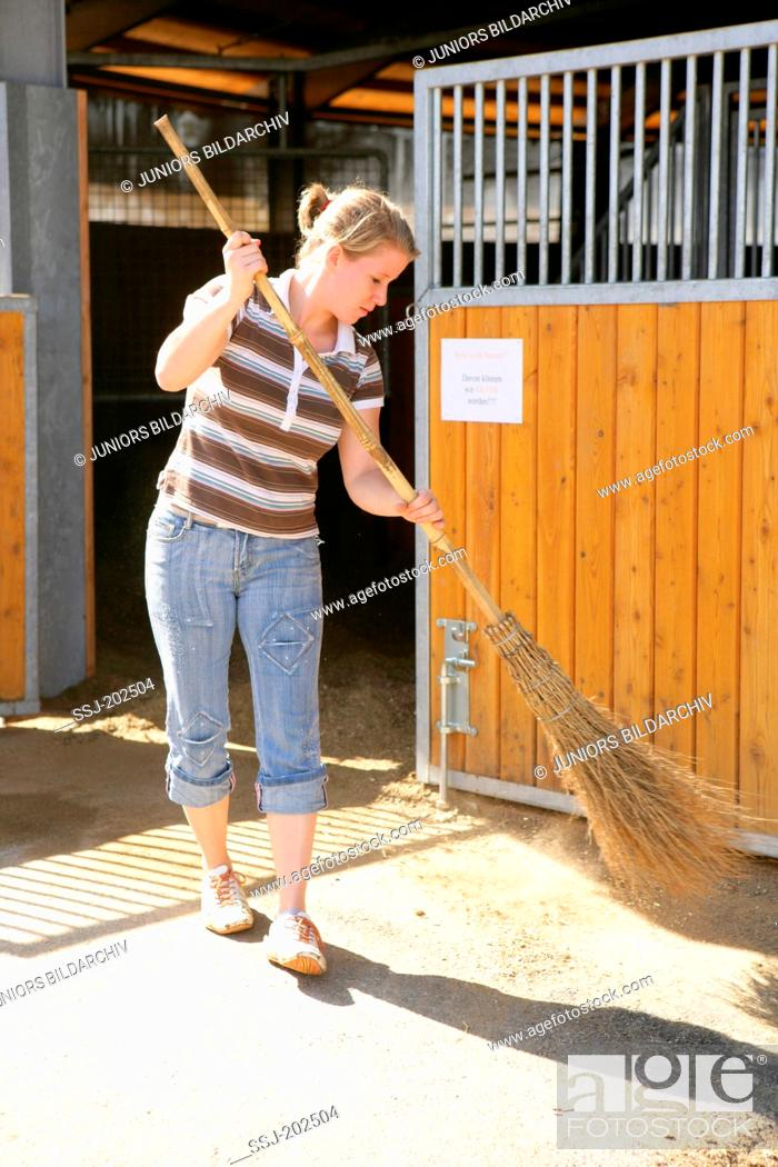 Girl sweeping the place in front of a riding hall with a