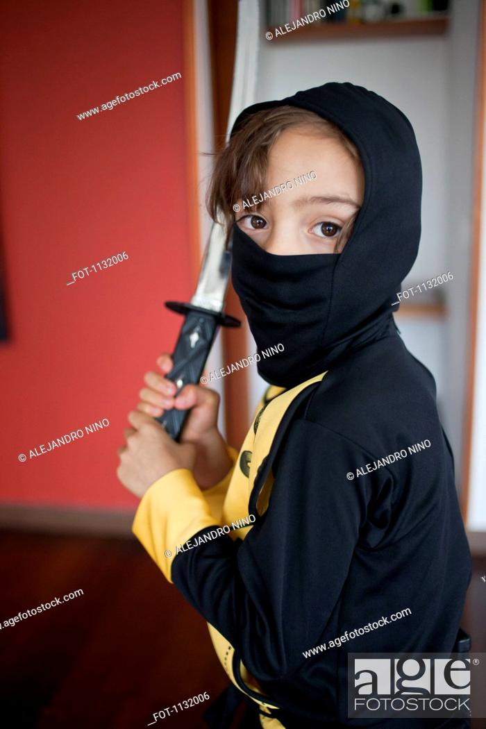 Stock Photo: A boy dressed in a ninja costume holding a samurai sword.