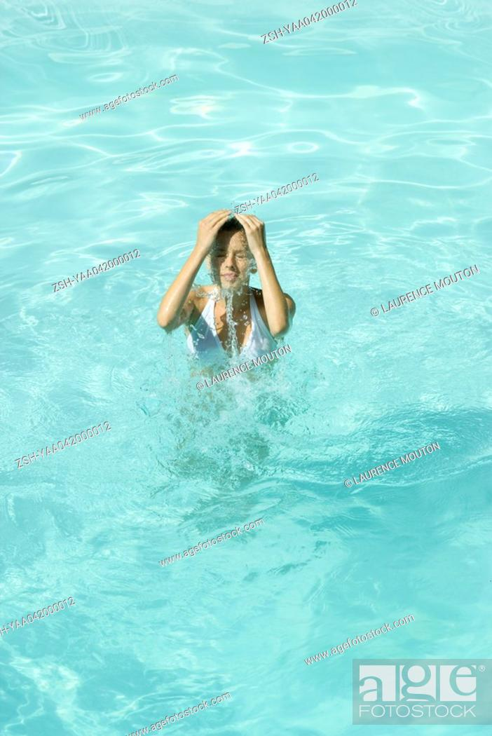 Stock Photo: Young woman splashing water over face in pool.