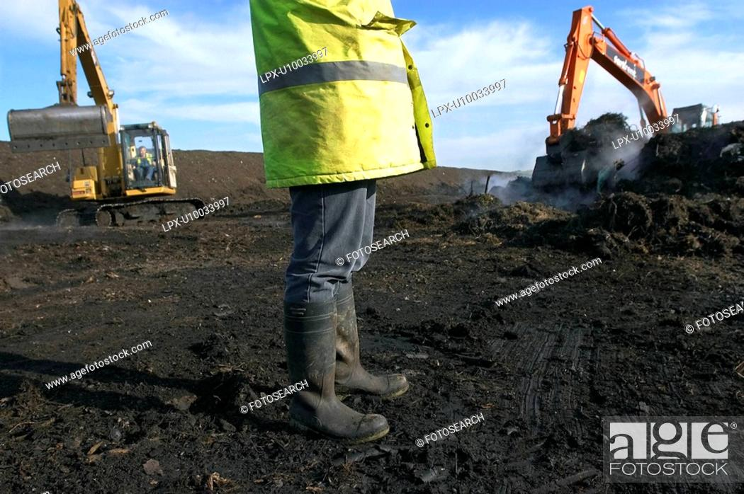 Stock Photo: Legs of site warden with tracked excavator on landfill.