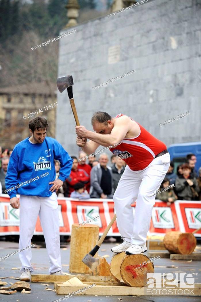 Stock Photo: 'Aizkolari' man cutting log with an axe, demonstration of 'aizkora' (traditional Basque sport). Mondragon, Euskadi, Spain.