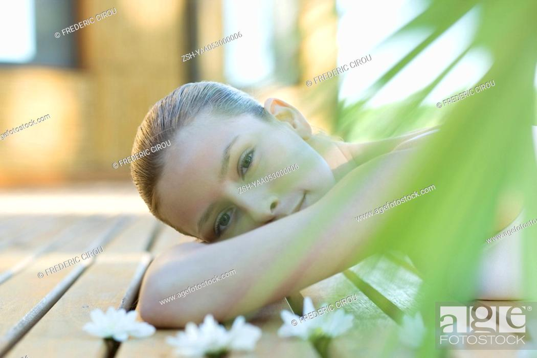 Stock Photo: Woman lying on deck, surrounded by flowers.